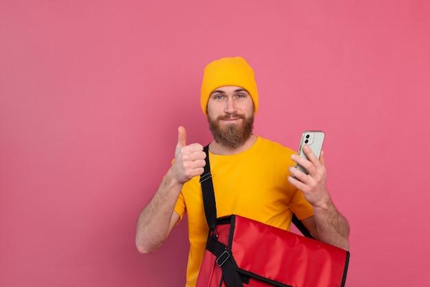 Fröhlicher europäischer lieferbote mit tasche lässig halten telefon auf rosa
