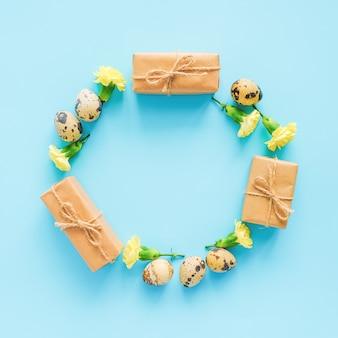 Fröhlicher festlicher kreisrahmen ostern. osterlayout gemacht von wachteleiern, gelben blumen und handwerksgeschenk auf blauem hintergrund mit kopienraum