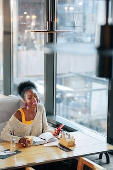 Fröhlicher freiberufler. fröhliche freiberuflerin, die ihr smartphone benutzt und kaffee trinkt, während sie im restaurant sitzt