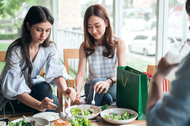 Fröhlicher freund, der lächelt und gesundes essen in einem restaurant isst