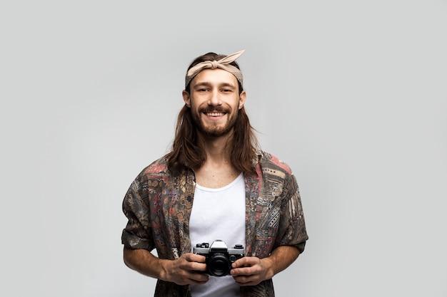 Fröhlicher freundlicher hippie mit einer filmkamera in den händen und einem verband auf dem kopf, einem freien, stilvollen und sorglosen hipster-reisenden-fotografen auf weißem hintergrund