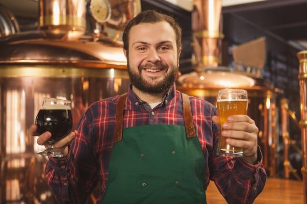 Fröhlicher freundlicher professioneller brauer in einer schürze, die glücklich zur kamera lächelt und zwei gläser bier hält