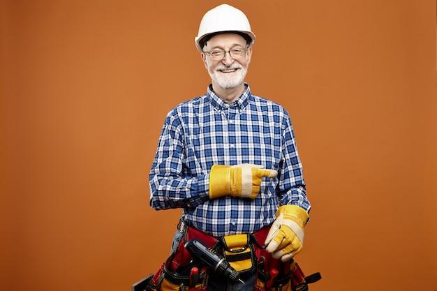 Fröhlicher, frinedly aussehender kaukasischer älterer männlicher zimmermann, der zeigefinger zeigt, der arbeitsausrüstung um taille trägt. lächelnder älterer bärtiger elektriker, der in schutzhandschuhen und werkzeuggürtel aufwirft