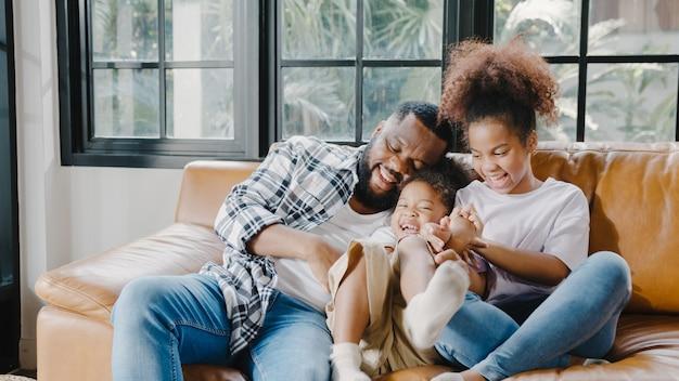 Fröhlicher, fröhlicher afroamerikanischer familienvater und tochter, die beim geburtstag im haus spaß beim kuscheln auf dem sofa haben.