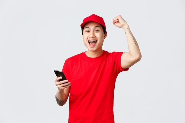 Fröhlicher, fröhlicher asiatischer lieferbote in roter uniformmütze und t-shirt des trägerdienstes, smartphone halten, gute nachrichten lesen, mit faustpumpe singen, ja schreien, sieg oder leistung feiern.