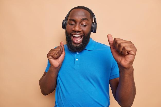 Fröhlicher fröhlicher bärtiger afroamerikanischer mann tanzt im rhythmus der musik macht fauststoß