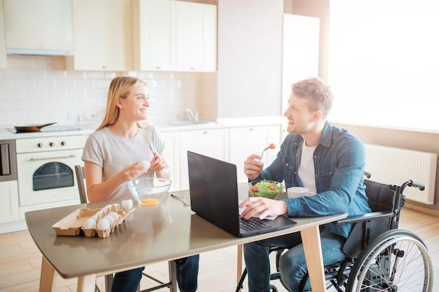 Fröhlicher, fröhlicher junger student mit behinderung und inklusion, der salat isst und studiert. er sieht frau an und lächelt. sie kocht. glückliches paar sitzt zusammen in der küche
