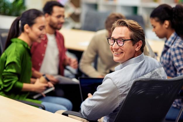 Fröhlicher, fröhlicher reifer geschäftsmann, der in die kamera lächelt, während er ein brainstorming-treffen mit hat?