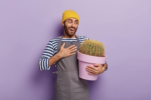 Fröhlicher gärtner, der mit einem großen topfkaktus aufwirft