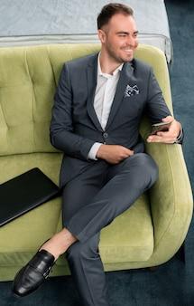 Fröhlicher geschäftsmann, der telefon verwendet, das im hotelzimmer mit koffer auf geschäftsreise sitzt