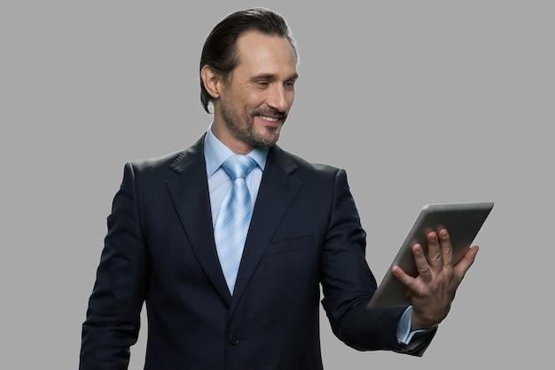 Fröhlicher geschäftsmann, der video-chat hat. lächelnder kaukasischer mann im geschäftsanzug, der glücklich durch digitale tablet-webcam spricht.
