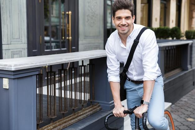 Fröhlicher geschäftsmann gekleidet im hemd, das auf einem fahrrad reitet