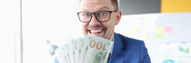Fröhlicher geschäftsmann hält bargeld in seinen händen schnelles einkommen ohne anlagekonzept