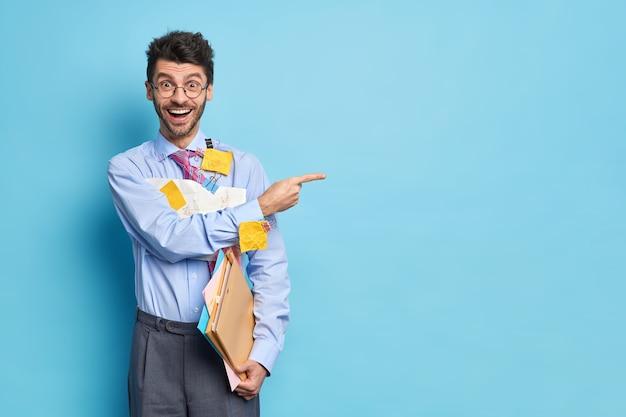 Fröhlicher geschäftsmann hält papiere mit diagrammen und formeln in formellen kleidern, zeigt glücklich weg auf blauem raum gibt empfehlung, wie man finanzbericht erstellt. mann analytiker drinnen