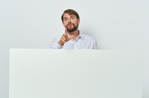 Fröhlicher geschäftsmann im hemd, das weiße werbetafel hält