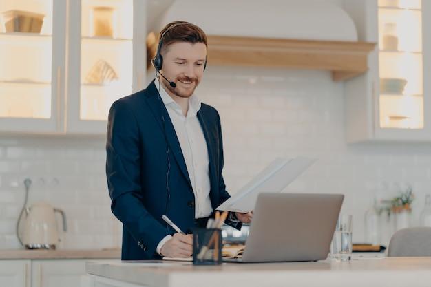 Fröhlicher geschäftsprofi im anzug, der papierblätter hält, informationen liest und während des online-meetings notizen macht, laptop und headset verwendet, während er zu hause arbeitet. remote-work-konzept