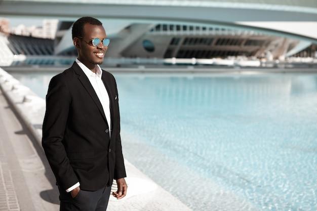 Fröhlicher glücklicher junger afroamerikanischer büroangestellter, der schwarzen eleganten anzug und stilvolle schatten trägt, die am städtischen brunnen stehen und hand in der tasche halten