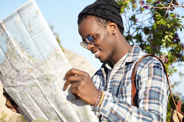 Fröhlicher glücklicher junger afroamerikanischer reisender, der trendigen blick sucht, der richtung auf lageplan sucht, wie man zum hotel kommt, während man im ausland in einem fremden stadt-hochsommerurlaub reist