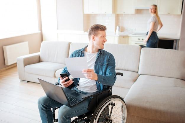 Fröhlicher glücklicher junger mann mit besonderen bedürfnissen blicken zurück. halten sie laptop ein stück papier. junge frau stehen am herd und kochen. sie schaut zurück auf ihn.
