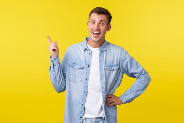 Fröhlicher glücklicher lächelnder kaukasischer mann, der mit dem finger auf die obere linke ecke zeigt und die kamera erfreut sieht. guy empfiehlt produktwerbung, spricht über ein tolles neues angebot, gelber hintergrund.