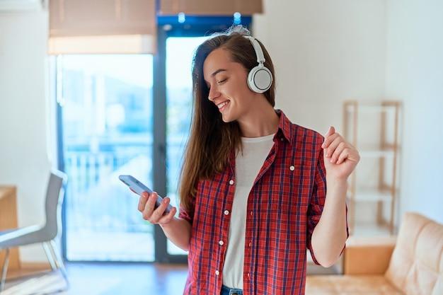 Fröhlicher, glücklicher mädchenmusikliebhaber mit geschlossenen augen, der das telefon hält und weiße drahtlose kopfhörer trägt, die musik hören und alleine zu hause tanzen. glücklicher moment leben