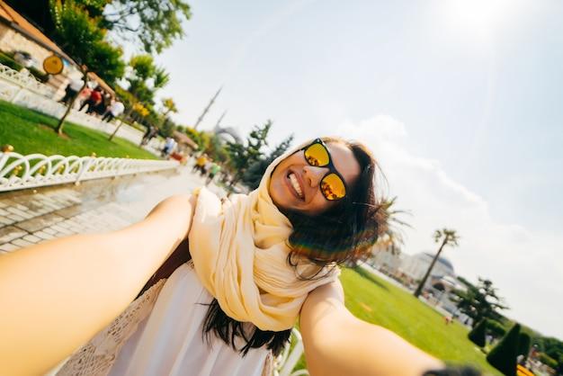 Fröhlicher, glücklicher mädchenreisender macht selfie, ein muslim mit brille, ein austauschstudent