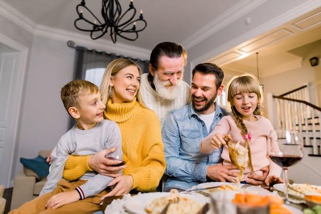 Fröhlicher grauhaariger großvater, enkelkinder, eltern, die am tisch sitzen, leckeres leckeres essen essen und spaß haben