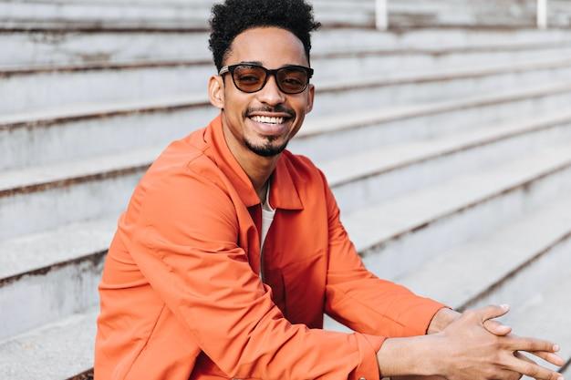 Fröhlicher gut gelaunter brunet-mann in sonnenbrille und orangefarbener jacke lächelt aufrichtig und sitzt draußen auf der treppe