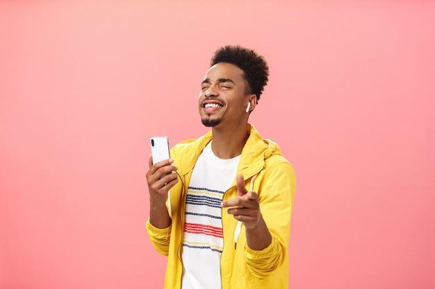 Fröhlicher, gutaussehender afroamerikaner mit afro-frisur und bart, die augen schließen und mit freude lächeln, musik in coolen drahtlosen kopfhörern zu hören, die das smartphone auf die kamera zeigen
