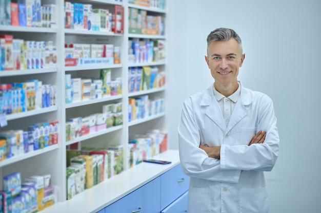 Fröhlicher gutaussehender apotheker posiert für die kamera am arbeitsplatz