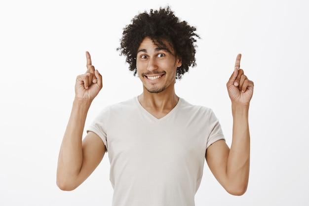 Fröhlicher gutaussehender dunkelhäutiger mann, der ankündigung macht, finger nach oben zeigt und banner zeigt