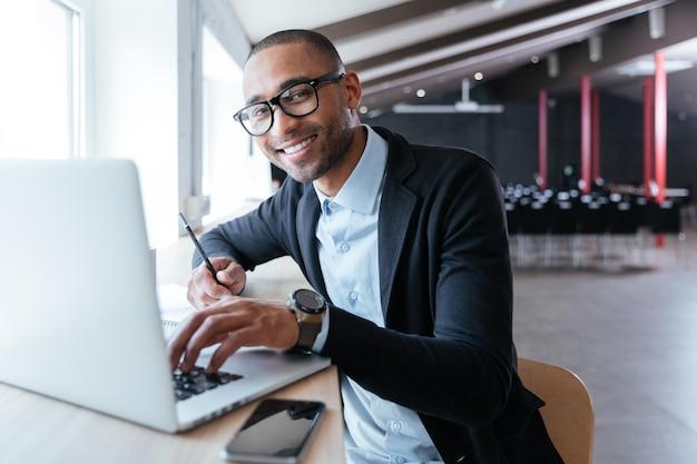 Fröhlicher gutaussehender geschäftsmann, der im büro an seinem laptop arbeitet