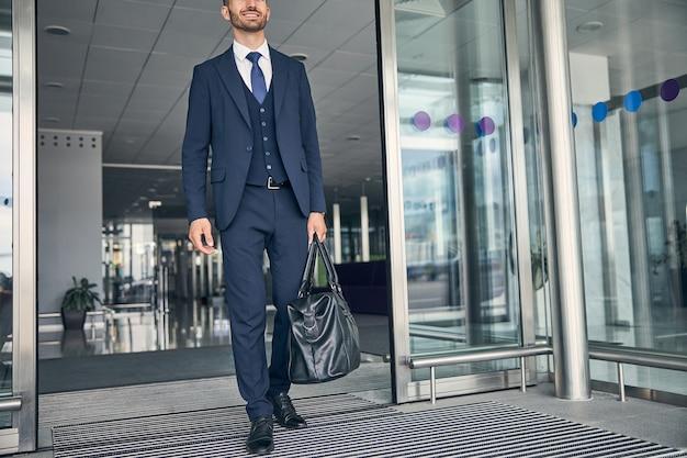 Fröhlicher gutaussehender geschäftsmann, der seine ledertasche trägt und lächelt, während er durch die tür geht?
