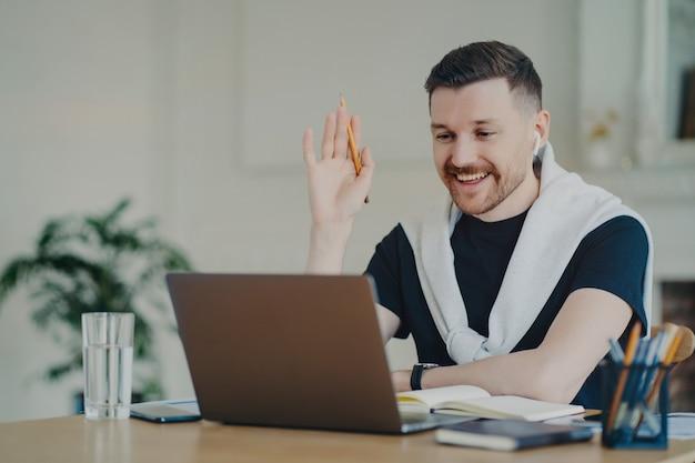 Fröhlicher, gutaussehender junger geschäftsmann oder männlicher freiberufler, der kopfhörer trägt, winkt mit der webcam auf dem laptop und sagt hallo zu seinen kollegen oder kunden während der videokonferenz, arbeitet im home office working