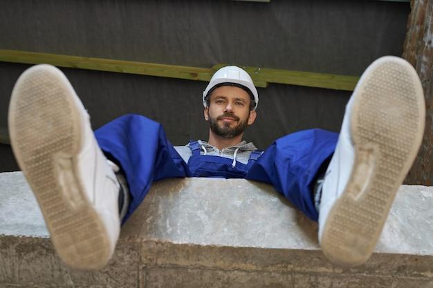 Fröhlicher, gutaussehender junger männlicher baumeister in blauen overalls und schutzhelm mit blick auf die kamera, der auf dem betonboden sitzt, während er am hausbau arbeitet