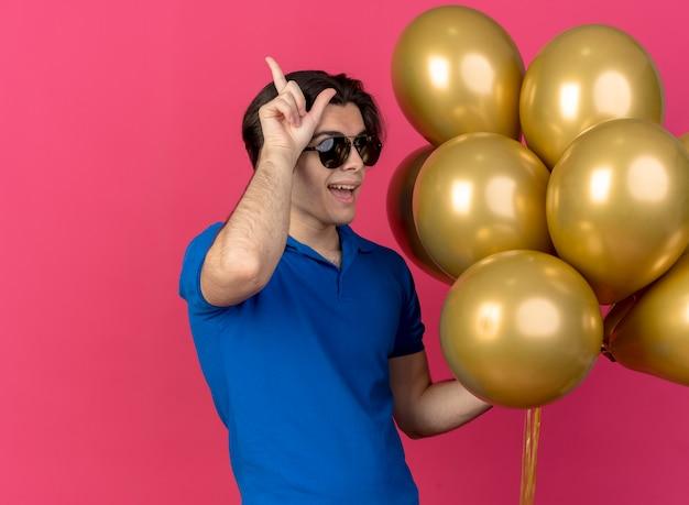 Fröhlicher gutaussehender kaukasischer mann in sonnenbrille hält heliumballons und gestikuliert verliererzeichen