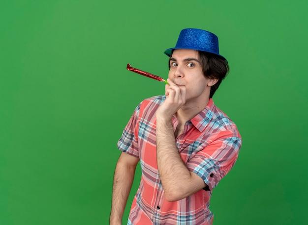 Fröhlicher gutaussehender kaukasischer mann mit blauem partyhut, der partypfeife bläst