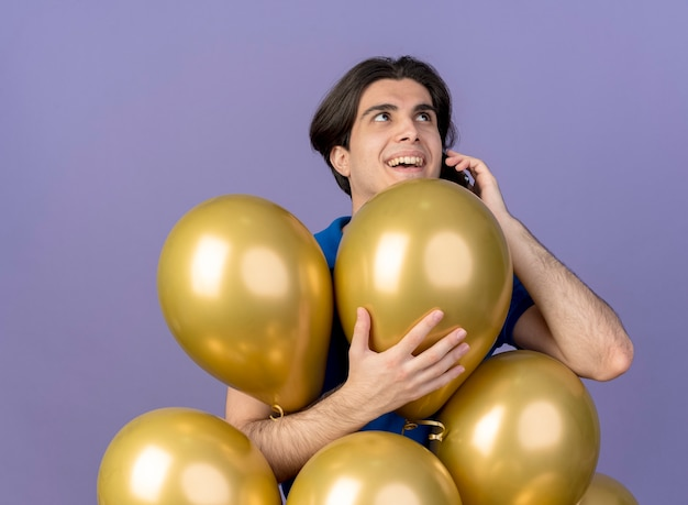 Fröhlicher gutaussehender kaukasischer mann steht mit heliumballons und telefoniert