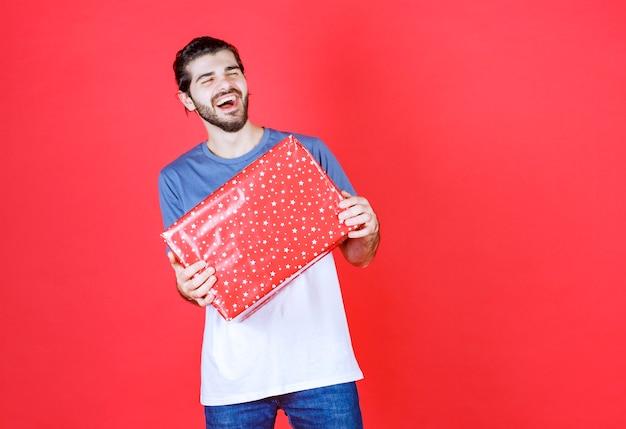Fröhlicher gutaussehender kerl, der eine große geschenkbox hält holding