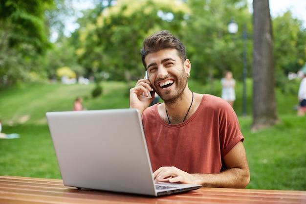 Fröhlicher gutaussehender mann, der laptop im park benutzt und glücklich am telefon spricht