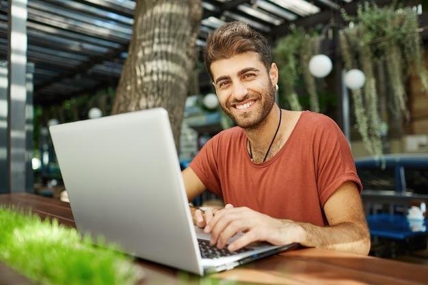 Fröhlicher gutaussehender mann, der mit freund online spricht, auf laptop tippt und glücklich lächelt