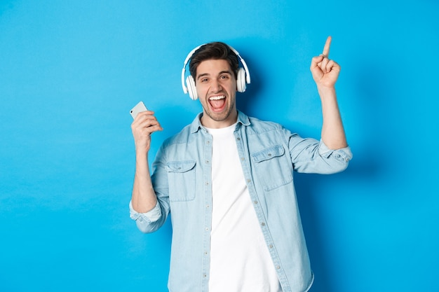 Fröhlicher gutaussehender mann, der mit smartphone tanzt, musik in kopfhörern hört und mit dem finger nach oben zeigt, auf blauem hintergrund stehend.
