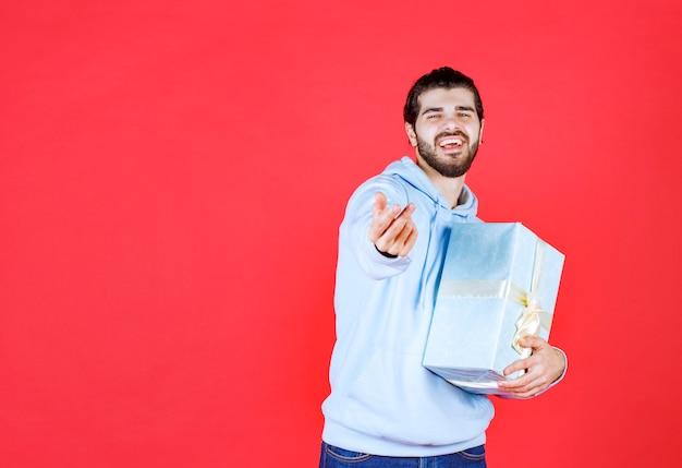 Fröhlicher gutaussehender mann, der verpackte geschenkbox hält und lächelt