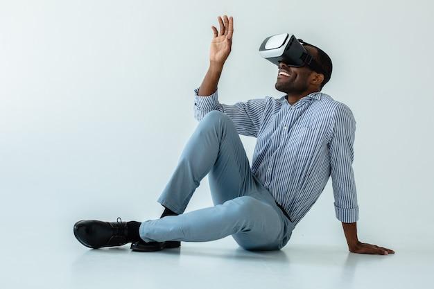Fröhlicher gutaussehender mann, der vr-brille benutzt, während er auf dem boden sitzt