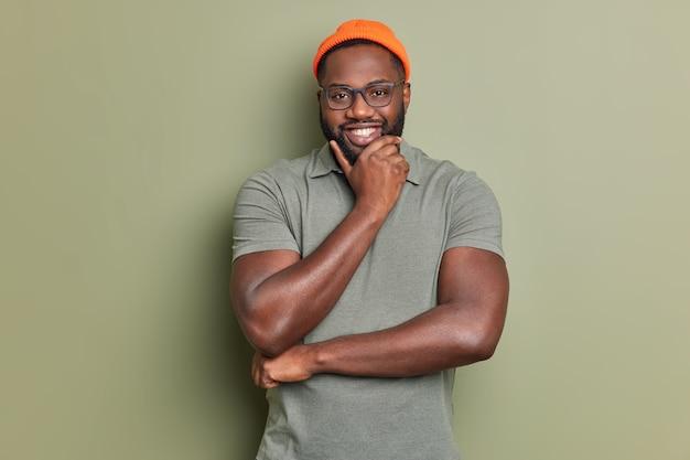 Fröhlicher gutaussehender mann hält kinnlächeln glücklich sieht selbstsicher vorne froh aus lob von chef trägt hut und lässiges t-shirt steht drinnen