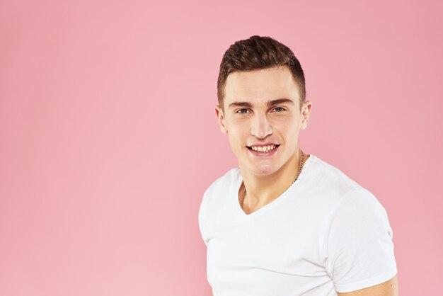 Fröhlicher gutaussehender mann im weißen t-shirt emotionen rosa isolierte wand.