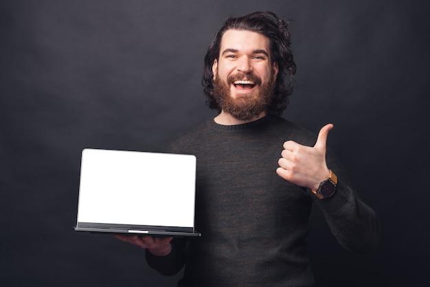 Fröhlicher gutaussehender mann mit bart in lässiger darstellung daumen hoch und laptop mit leerem bildschirm copyspace