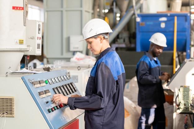 Fröhlicher gutaussehender wurm in bauarbeiterhelm, der am geländer steht und mit kollegen während der pause in der fabrik plaudert