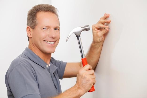 Fröhlicher handwerker. fröhlicher grauer haarmechaniker, der einen nagel hämmert und in die kamera lächelt
