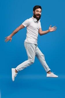 Fröhlicher hipster, der springt und kamera betrachtet